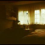 Eines der Mansardenzimmer mit Bett, Schreibtisch und Wandregal. Für die insgesamt zwölf Gästezimmer gab es im gesamten Haus zwei Bäder. 1971.