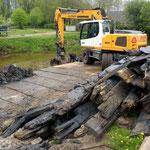De kraan verwijdert de oude beschoeiing van de haven