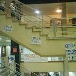 Carteles colgados en la escalera del hall. El de la derecha contiene insultos.