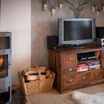 Wohnzimmer mit Fernseher und Kamin