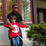 Kind und Juan zwischen Sträuchern mit Hilfe des Stockes: