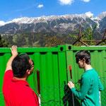 Die Höhe eines Containers hinter einem Maschendrahtzaun erklicken: