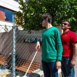 Gemeinsam ein Gebäude hinter einem Zaun erklicken: