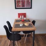 Zona comedor de cabaña roja, compuesta por mesa de tapa de madera con patas de hierro negro, sillas de diseño negras, cuadro rojo y negro, individuales rústicos de apoyo, aceitera, vinagrera, salero y pimentero