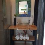 Toilette de cabaña esmeralda, de tapa de madera y patas de hierro, con bacha de vidrio y griferia de diseño plateada. Espejo de diseño y secador de cabello
