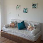 Zona estar de cabaña esmeralda, con sofa cama con almohadones de motivos bulgaros y esmeralda, adaptable a cama individual