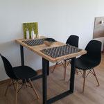 Zona comedor de cabaña esmeralda, compuesta por mesa de tapa de madera con patas de hierro negro, sillas de diseño negras e individuales rústicos de apoyo