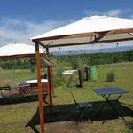 Pergolas con mesas y sillones para disfrutar el paisaje de Los Reartes desde el parque de las cabañas