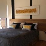 Zona dormitorio de cabaña dorada, compuesta por cama queen con cubrecama gris y almohadones dorados y cuadro dorado y negro