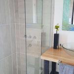 Ducha de cabaña esmeralda, con piso y paredes de porcelanato, mampara de vidrio y griferia de diseño