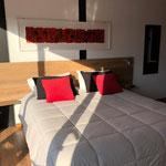 Zona dormitorio de cabaña roja, con cama queen de cubrecama acolchado gris y almohadones negros y rojos. Cuadro de madera pintado en acrilicos rojos y negros
