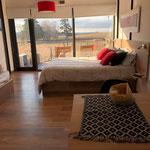 Zona comedor y dormitorio de cabaña roja, compuesta por cama queen, sofá cama y mesa comedor