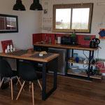 Zona cocina comedor de cabaña roja. compuesta por mesa de madera con patas de hierro negro, sillas de diseño negras, lamparas colgantes y kitchenette completa