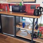 Zona cocina de cabaña roja, compuesta por anafe, microondas, pileta de lavar, escurridor de platos, heladera bajomesada y vajilla completa para 3 personas