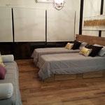 Zona dormitorio de cabaña dorada, adecuada a 3 camas individuales con cubrecama gris y almohadones dorados y cuadro dorado y negro