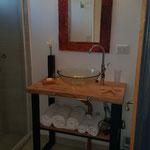 Toilette de cabaña roja, de tapa de madera y patas de hierro, con bacha de vidrio y grifería de diseño plateada. Espejo de diseño y secador de cabello