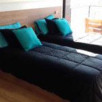 Zona dormitorio de cabaña esmeralda, adecuada a 2 camas individuales con cubrecama negro y almohadones esmeralda y cuadro esmeralda y negro