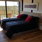 Zona dormitorio de cabaña roja, adaptada a 2 camas individuales con cubrecama acolchado negro y almohadones negros y rojos. Cuadro de madera pintado en acrilicos rojos y negros