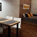 Zona comedor y dormitorio de cabaña amarilla, compuesta por cama queen, sofá cama y mesa comedor