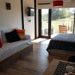 Zona estar de cabaña roja, con sofa cama con almohadones en tonos rojos, anaranjados y amarillos, adaptable a cama individual. Smart TV de 32 pulgadas con Netflix