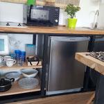 Zona cocina de cabaña esmeralda, compuesta por anafe, microondas, pileta de lavar, escurridor de platos, heladera bajomesada y vajilla completa para 3 personas