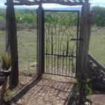 Puerta de bajada al rio, hecha a mano, con dibujos de hierro de montañas y flores. Vista a las sierras grandes y al Champaqui