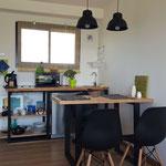 Zona cocina comedor de cabaña esmeralda. compuesta por mesa de madera con patas de hierro negro, sillas de diseño negras, lamparas colgantes y kitchenette completa