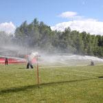 Hinter einem Feuerwehrschlauch steckt eine Menge Wasserdruck. Mit zwei Mann müssen die Jugendfeuerwehrmitglieder daher auf den Kanister zielen.