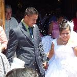 Des mariés sous une pluie de riz à la sortie de l'église