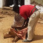Boucher qui découpe sa viande sur la rue