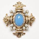 Лот №П604.Винтажная брошь-мальтийский крест от компании Cadoro,в отличном состоянии,маркирована.Ювелирный сплав под состаренное золото,искусственный жемчуг,центральный элемент из голубого люцита.Размер-5х4.5 см.ПРОДАНА