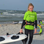 Luzie schleppt ihr großes Board vom Strand.