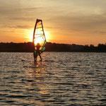 Antonia zu Hause beim Windsurfen im Sonnenuntergang.