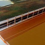 Encuadernado cosido visible, con hilo naranja.