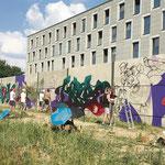 August: Vor der Flüchtlingsunterkunft in der Paul-Schwenk-Straße verwandeln nationale und internationale Künstler gemeinsam mit Kindern und Jugendlichen aus dem Bezirk eine 180 Meter lange Schallschutzwand in eine der größten Graffiti-Galerien Berlins.