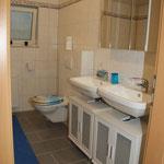 Badezimmer mit zwei Waschbecken, Dusche und WC