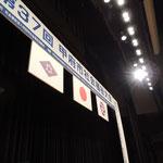 来賓席から見たステージ看板(どん帳が上がる前に撮影しました)