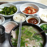 Dwaeji Gukbap (Reissuppe mit Schweinebauch) mit verschiedene Beilagen