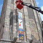 4. Station: Kroatien, Montage von Fahnen an der Wand eines Kirchturmes