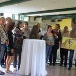 """Austellende KünstlerkollegInnen, die Betreuerin der Spendenbox für die Ausstellungsdauer und Pastellbild """"I´m yours"""""""