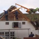 Mit dem Kran werden die Balken durch das offene Dach gehoben und geschoben