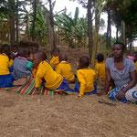 Kinder im Garten mit einer Betreuerin bei der Teepause.