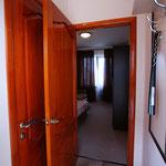 Небольшой коридор-прихожая с зеркалом и вешалкой, рядом вход в душ-туалет .
