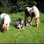 Fast wie Geschwister... Pause auf der Wiese für Reiter und Ponies.