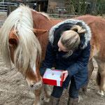 Jassi zeigt Jette, was es da so an Leckereien in der Weihnachtsdose gibt.