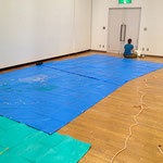 下準備で床面にブルーシートを。広い展示室なのに、なぜか隅っこでミシンの準備をする太田さん