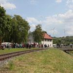 Der Zug aus Hohanau wird beim Regionsfest in Hauskirchen bereits erwartet. Leute verteilen sich am Platz und auf der Brücke, um den Zug aus Hohenau zu empfangen.