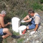 Karl und Heinrich streichen die Hektometersteine.