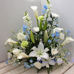 白いユリに淡いブルーの花を入れて 生花のお悔やみの花