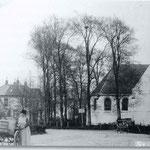 Foto van vermoedelijk rond 1915. We kijken in zuidelijke richting. De wegwijzer wijst naar Schagen (via de Twuyverweg) en naar Alkmaar (via de Bovenweg). De vrouw met de melkkar is Anne Roos.